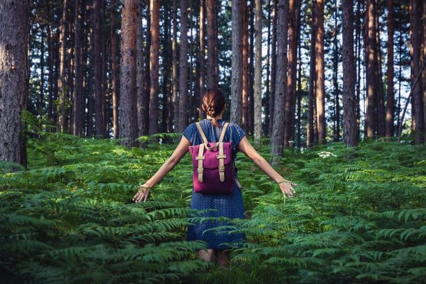 Woman walking in nature forest fern